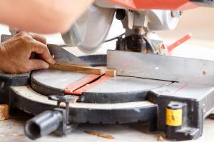Home Repair - carpenter cut wood for house construction